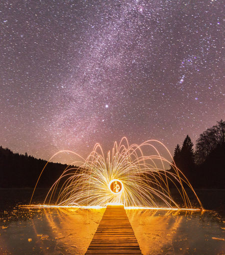 Wire Wool On Jetty Over Lake Against Starry Sky