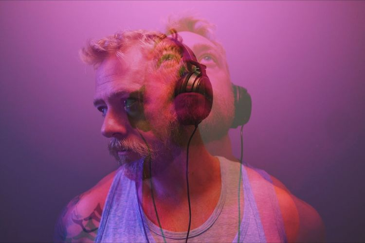 Double exposure of man listening to music
