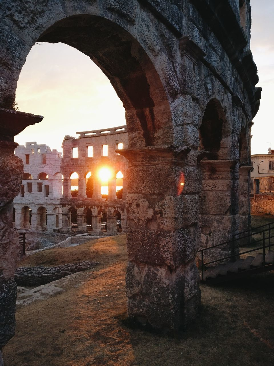 arch, built structure, architecture, history, ancient, old ruin, flame, sunset, no people, indoors, travel destinations, building exterior, illuminated, sky, day, ancient civilization