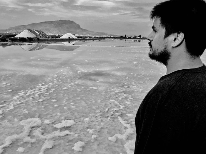 Side view of young man looking away in sea against sky