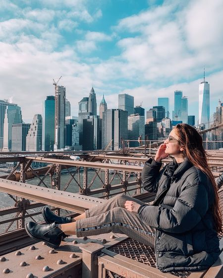 Woman sitting on bridge against cityscape