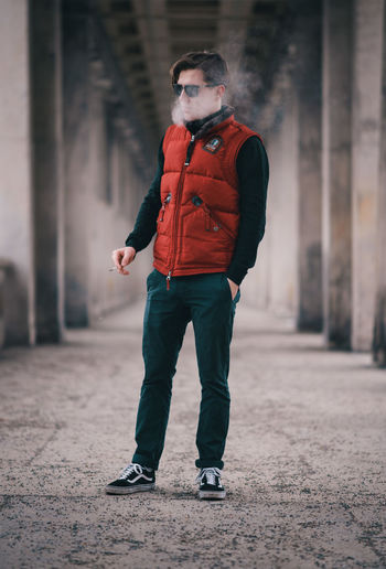Full Length Of Young Man Smoking While Standing In Corridor