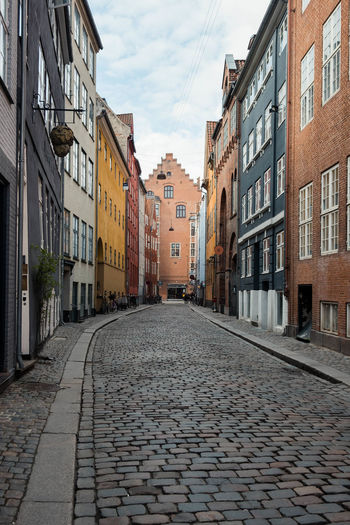 Copenhagen, Denmark Old Street Apartment Architecture Building Building Exterior Built Structure City Cloud - Sky Cobblestone Copenhagen Day Direction Footpath Nature No People Outdoors Paving Stone Residential District Row House Sky Street The Way Forward Town Window