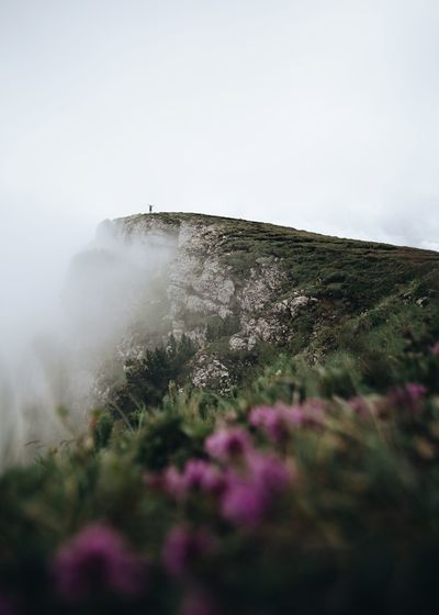 Low angle view of cliff against sky at bucegi natural park