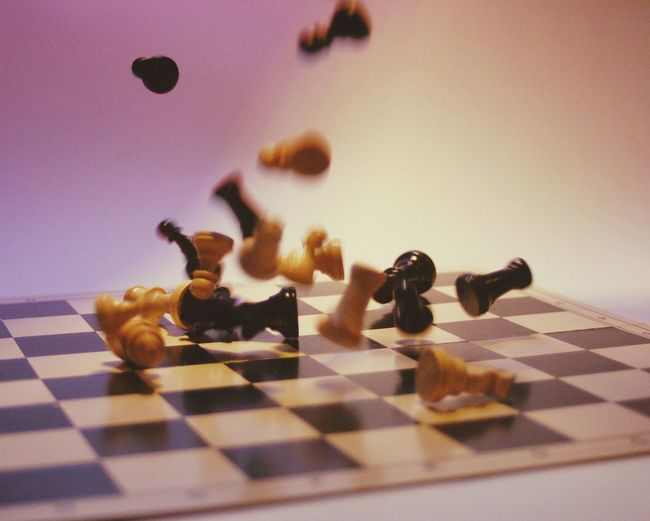 Close-up of chess piece falling on board falling against colored background