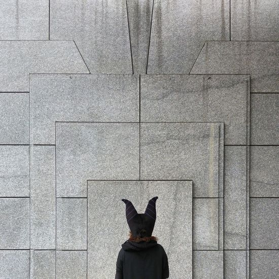 Rear view of woman in animal mask in front of wall