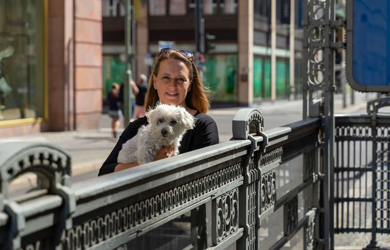 Portrait of woman with dog on railing