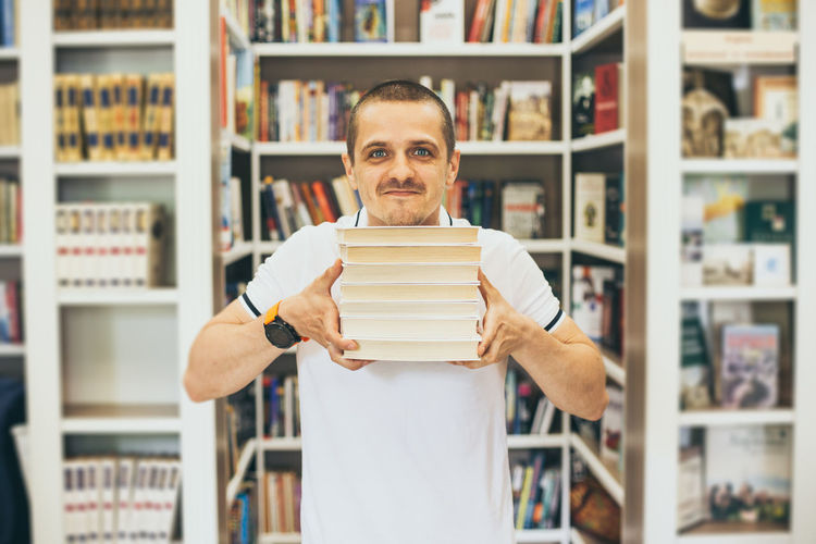 Portrait of man holding books in library