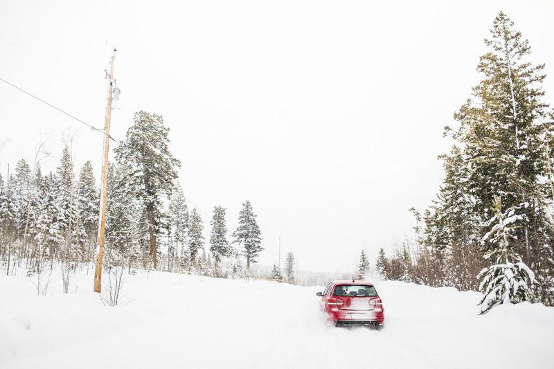 Car on snow covered land against sky