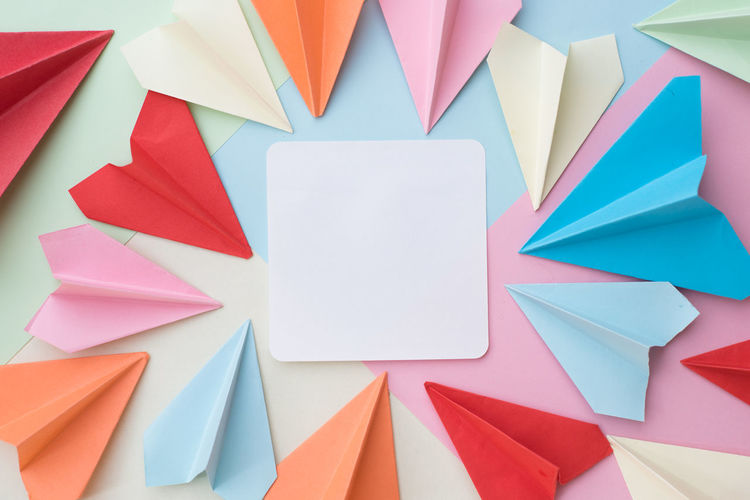 Directly above shot of blank paper with colorful origami airplanes on table