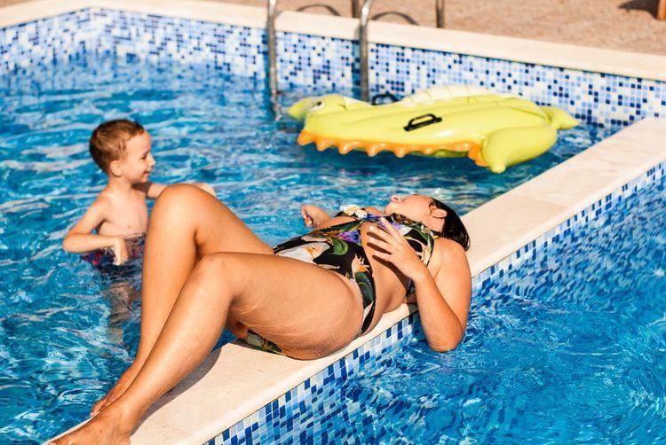 Young woman lying on railing in swimming pool