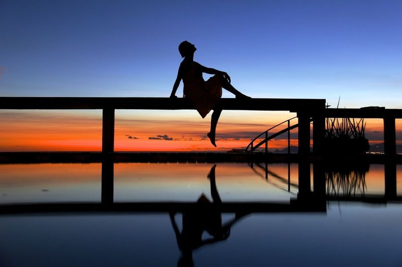 Silhouette woman on railing reflecting in water during sunset