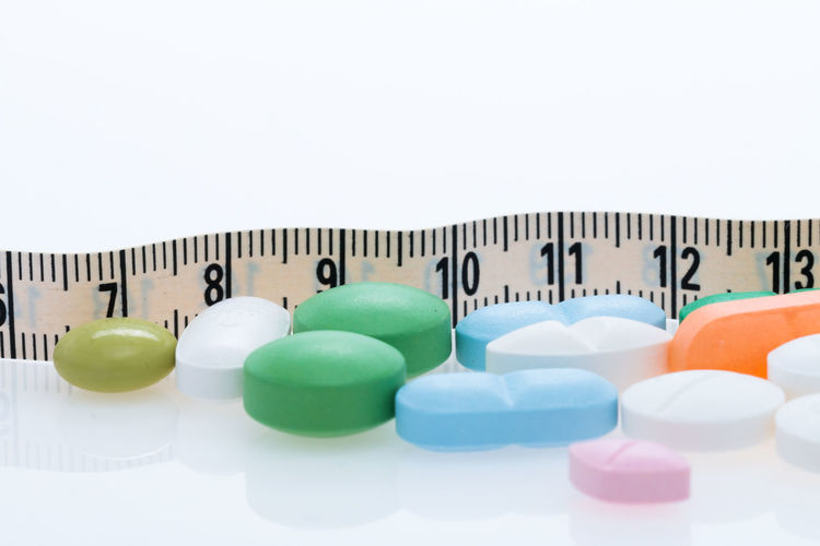 Medicines with tape measure over white background