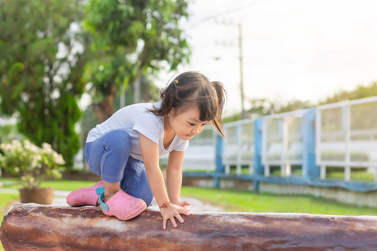 Full length of girl sitting on play equipment at park