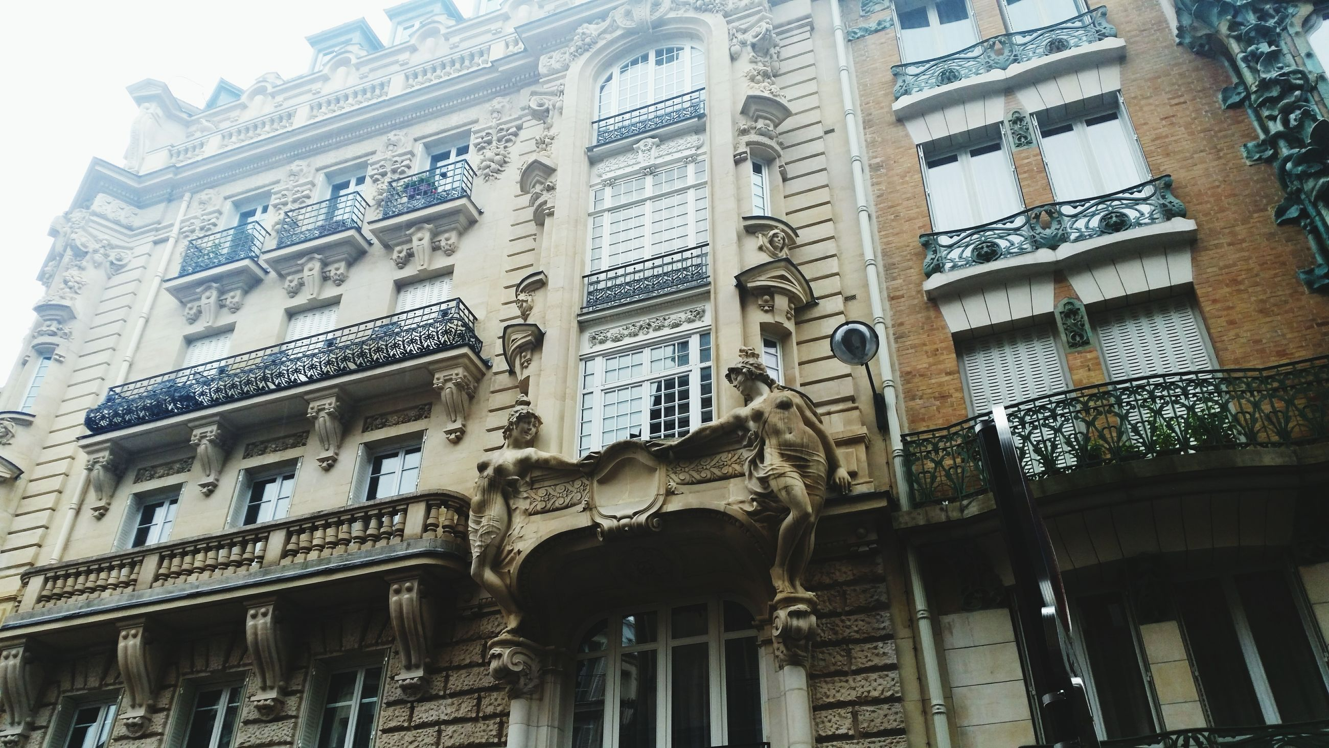 architecture, building exterior, built structure, low angle view, window, building, city, text, facade, residential building, sky, day, outdoors, art and craft, no people, residential structure, human representation, balcony, western script, arch