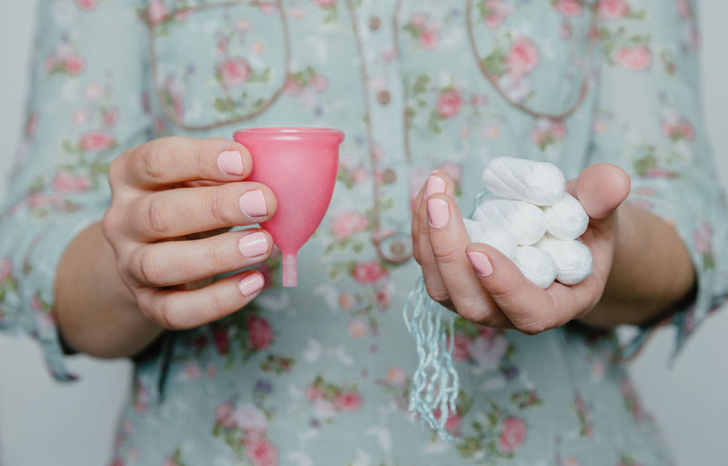 Midsection of woman holding tampon with menstrual cup
