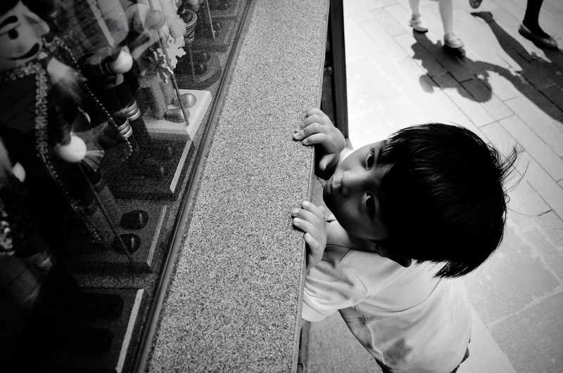 High angle view of boy looking at toys in display cabinet