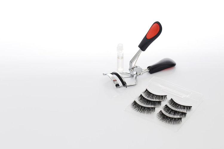 False eyelashes with curler on white background