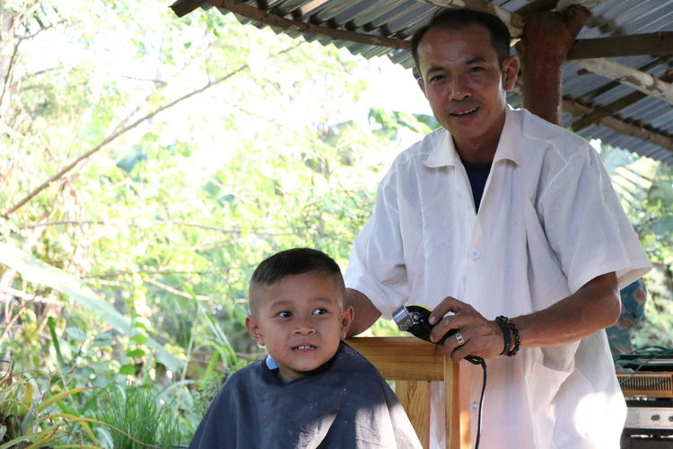 Portrait of mature barber trimming boy hair at shop against trees
