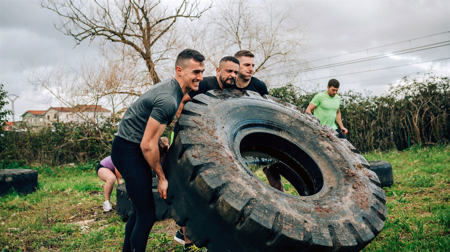 Male friends picking up tire at boot camp