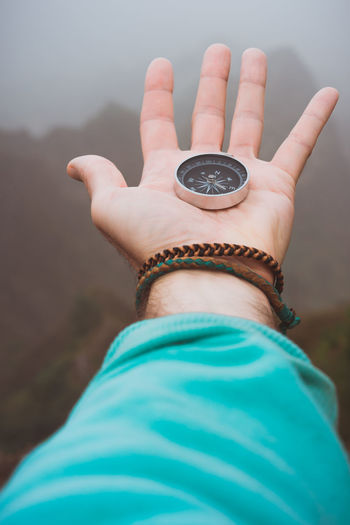 Hand with compass on the rock in front of the monumental mountain range silhouette in the fog. Cape Verde Adult Body Part Close-up Compass Day Finger Fingers Focus On Foreground Hand Haze Human Body Part Human Finger Human Hand Leisure Activity Lifestyles Nature One Person Open Outdoors Personal Perspective Real People Selective Focus Showing Streching