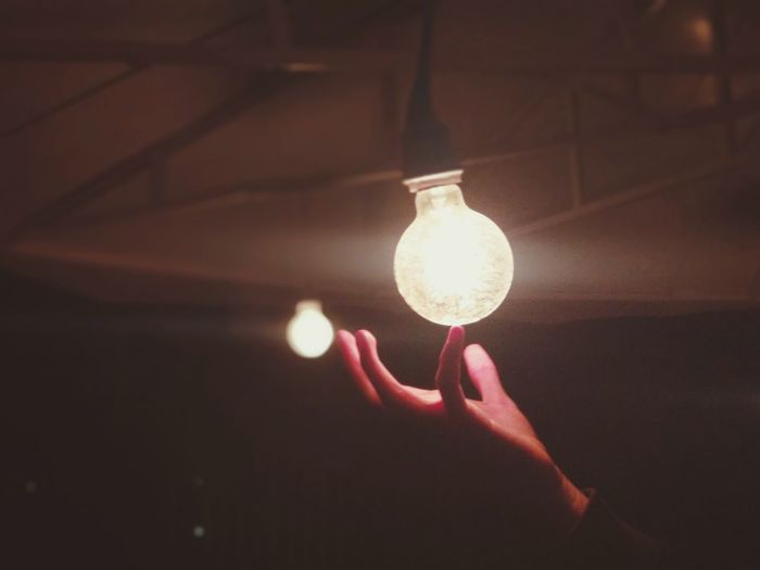 Cropped hand holding illuminated light bulb in darkroom