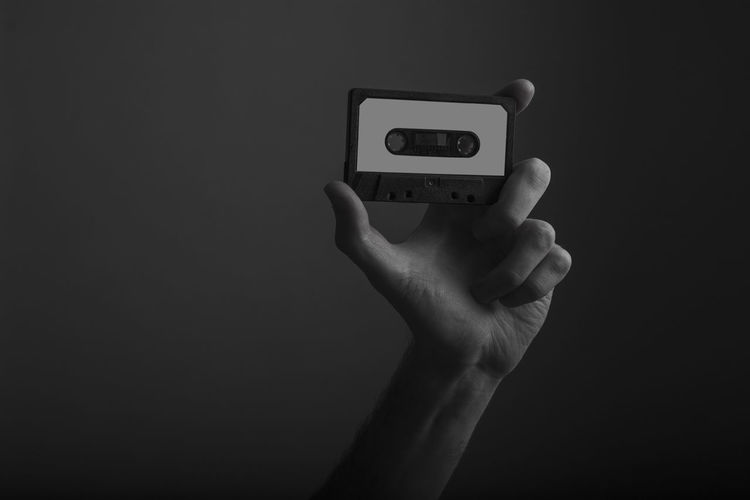 Close-up of hand holding telephone against black background
