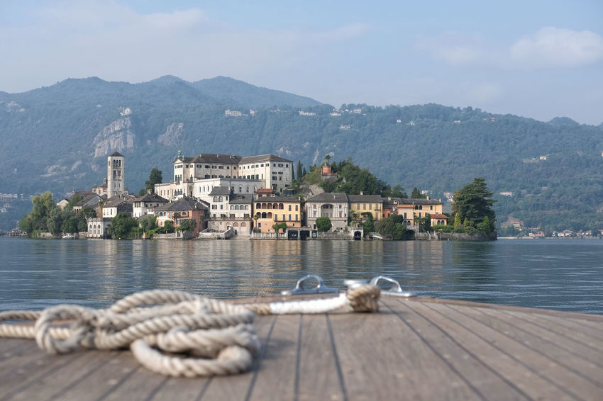 view from the motorboat of San Giulio island on the Orta lake in Italy Orta  Orta S.Giulio Panorama From The Boat Island Island On The Lake Italian Lake Italy Lago Orta Lake Landscape Motorboat Mountain No People Orta Lake Orta San Giulio Outdoors Scenics Sunny Day Tourist Destination Travel Destinations Water