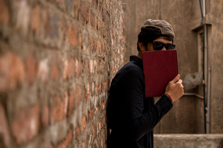 Portrait Of Man Covering Face With Book While Standing By Brick Wall