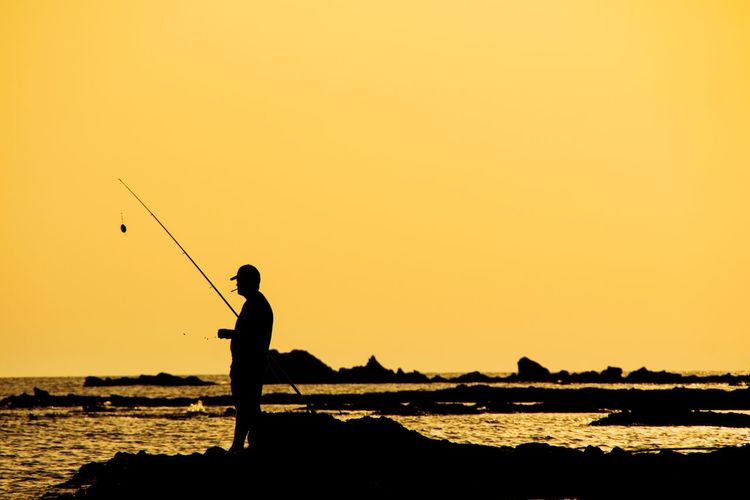 Silhouette Man Fishing At Beach Against Orange Sky