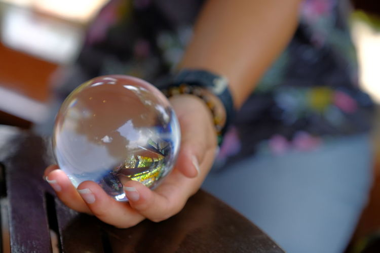 Midsection of woman holding crystal ball