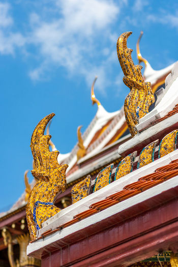 Detail of the traditional golden ornaments on a roof at the Wat Phra Kaew Palace, also known as the Emerald Buddha Temple. Bangkok, Thailand. Architecture Bangkok Thai Thailand Wat Phra Kaew Architecture Art And Craft Belief Buddhism Building Exterior Cloud - Sky Landmark Low Angle View Outdoors Place Of Worship Religion Royal Palace Sculpture Sky Spirituality Statue Travel Destinations