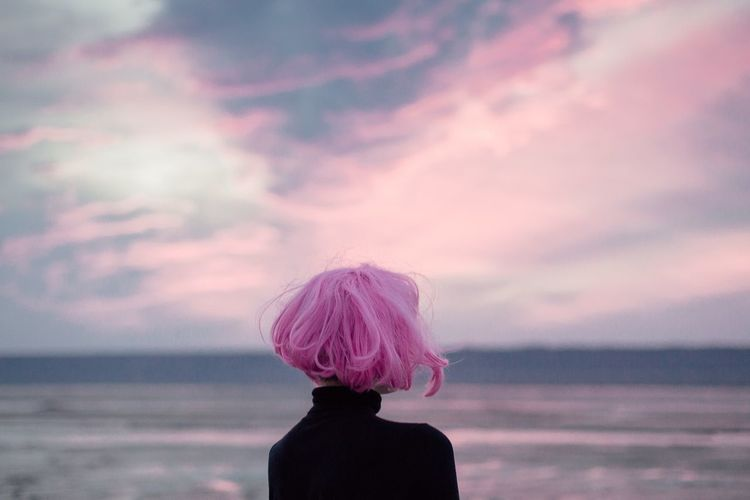 Woman with pink hair standing at beach against sky during sunset