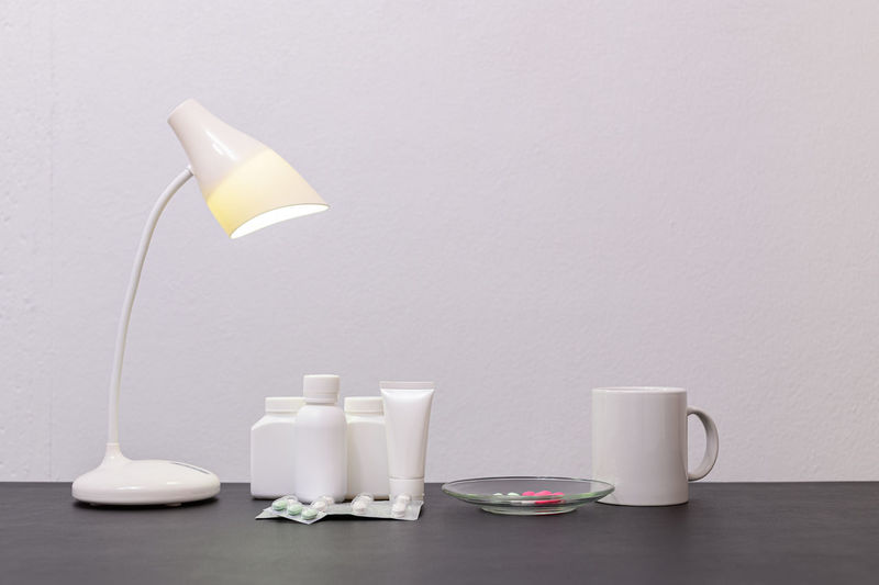Coffee cup on table against white wall