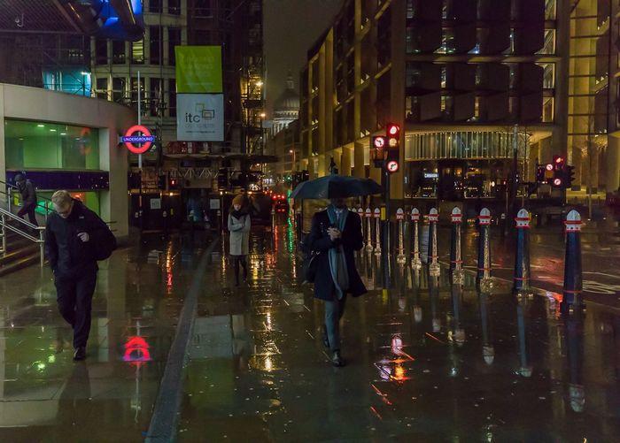 People on wet street in city during rainy season