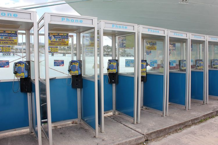 Public Telephones on Antigua Public Telephone Booth Public Telephone Architecture Blue Built Structure Communication Day In A Row Metal No People Outdated Tech Outdoors Public Telephones Railing Side By Side Sign Technology Text