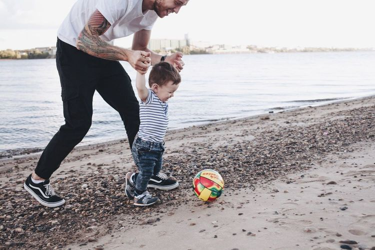 Tattoo Life Low Section Water Lifestyles Leisure Activity Shoe Beach Men Casual Clothing Footwear Human Foot Person Togetherness Shore Sea Day Focus On Foreground Vacations Non-urban Scene Outdoors Family Fatherhood Moments Father & Son