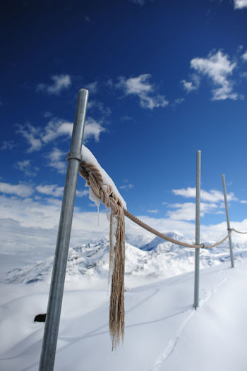 Close-Up Of Fence On Snow Covered Mountain Against Sky