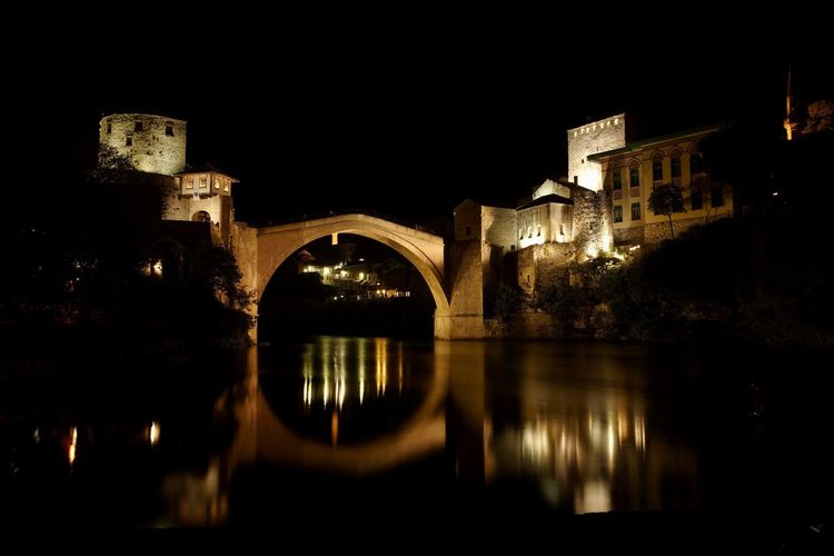 Illuminated arch bridge over river by buildings in city at night