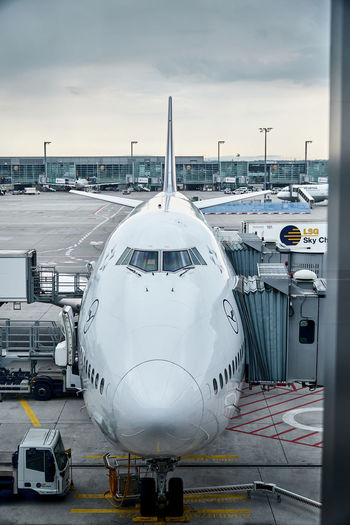 Parked Airplane Air Vehicle Mode Of Transportation Airplane Transportation Airport Travel Commercial Airplane Airport Runway Passenger Boarding Bridge Public Transportation Sky Stationary Cloud - Sky Airport Departure Area Aerospace Industry Land Vehicle Airport Terminal Arrival