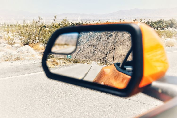 Road reflecting on side-view mirror of car