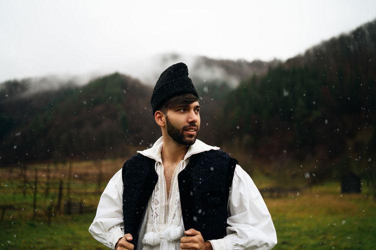 Man wearing warm clothing looking away while standing on land