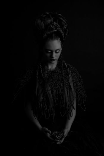 Young woman in costume standing against black background