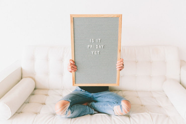 A young woman holding a sign that says 'is it Friday yet?'. Monday Sign barefoot Bed Bedroom Communication Day Home Interior Indoors  Low Section One Person People Real People Sitting Text Western Script