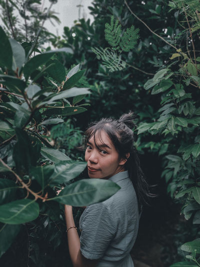 Portrait of beautiful young woman standing by plants