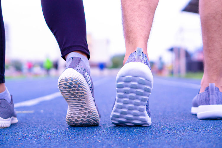 Low section of couples wearing sports shoes on running track