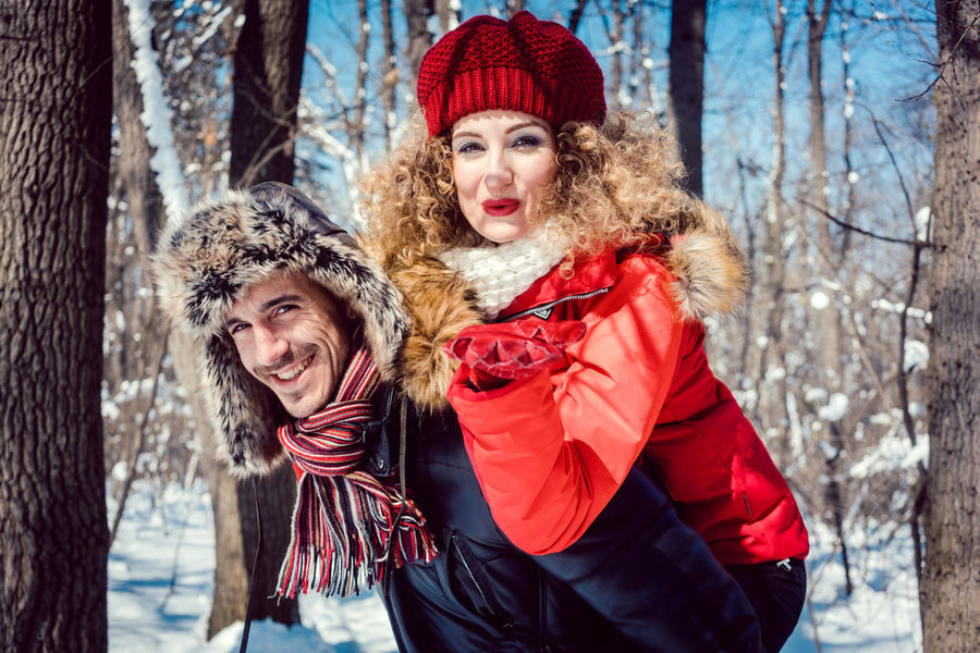 Woman and man, a couple, enjoying a winter walk in the sun on a cold day Carrying Couple Love Man Piggyback Sunny Walk Winter Walk Woman Adult Beauty Blowkiss Embracing Happiness Nature Outdoors Red Scarf Smiling Snow Walking Warm Clothing Winter