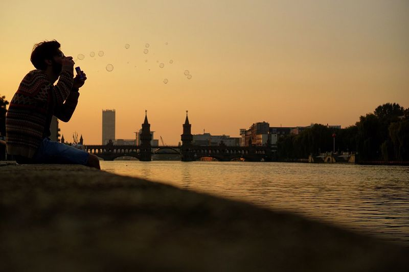 Side View Of Man Blowing Bubbles By Oberbaum Bridge Against Clear Sky During Sunset