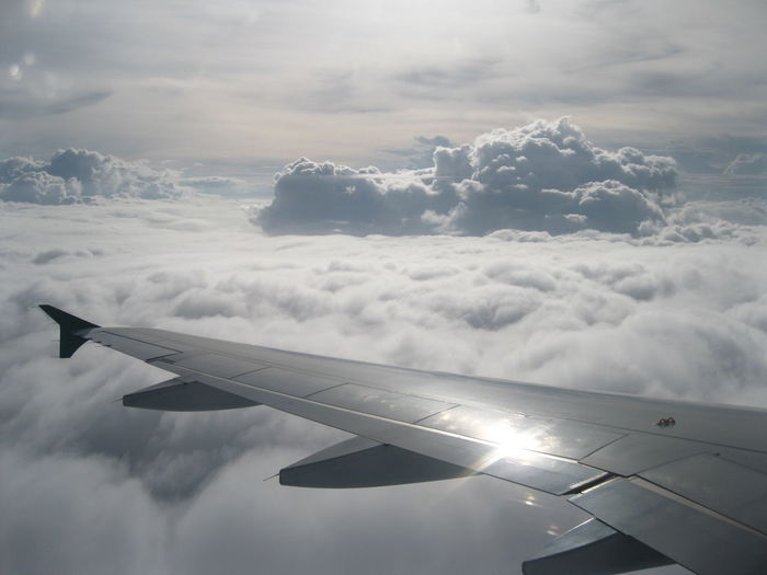 View of airplane wing over clouds