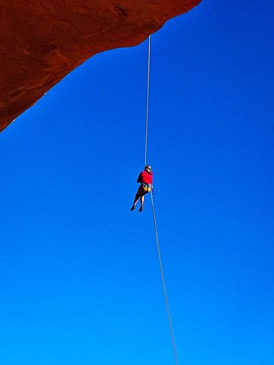 Low Angle View Of Person Climbing On Rope Against Clear Blue Sky